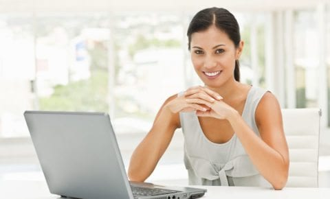 Happy pretty female executive by a laptop with lots of copyspace